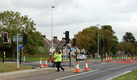 Workers remove traffic cones and signage to bring a new bus lane into operation.