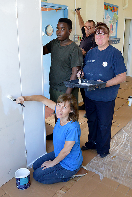 Photo of Tesco staff and local volunteers helping to decorate St Chad's Church Hall, Patchway.