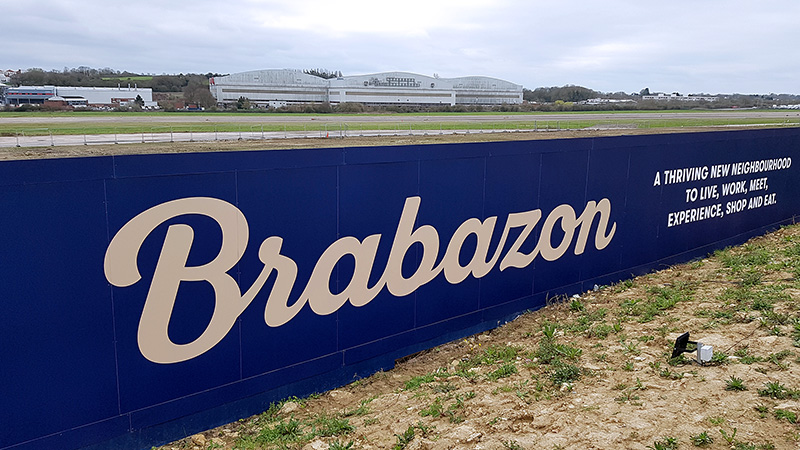 Photo of an advertising hoarding for the Brabazon development, with the Brabazon hangars visible in the background.