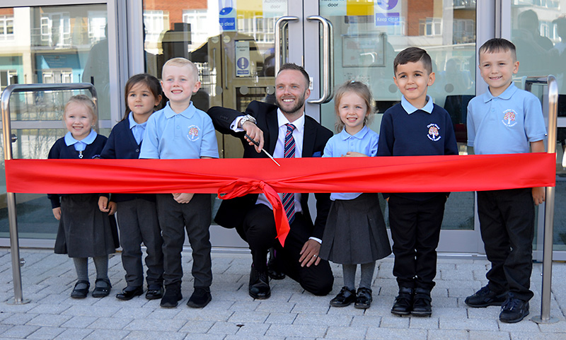 Photo of headteacher Neil Lankester cutting the ceremonial ribbon.