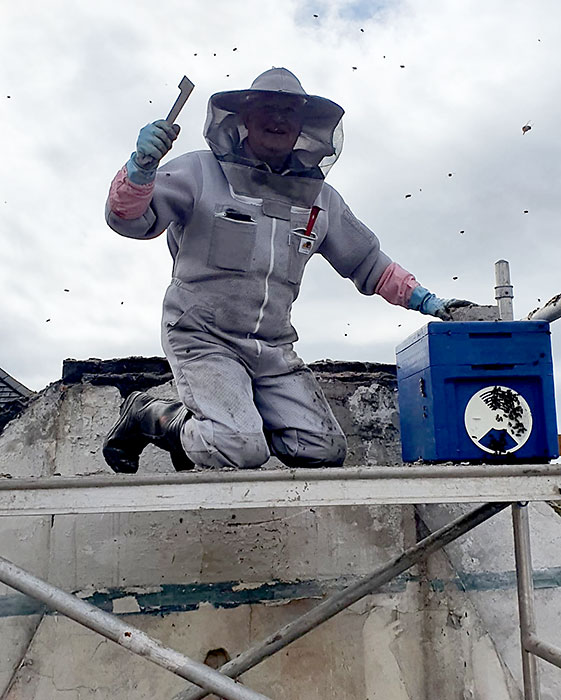 Photo of an apiarist on a roof.